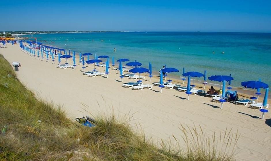 De Adriatische Zee met bedjes en parasols